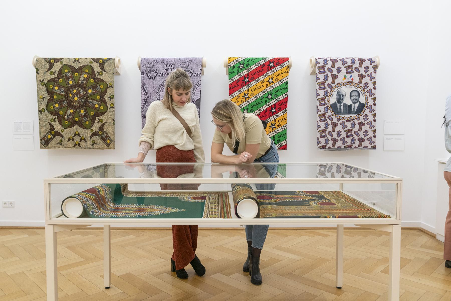 zwei Frauen stehen vor einer Vitrine, in der zwei Teppiche liegen