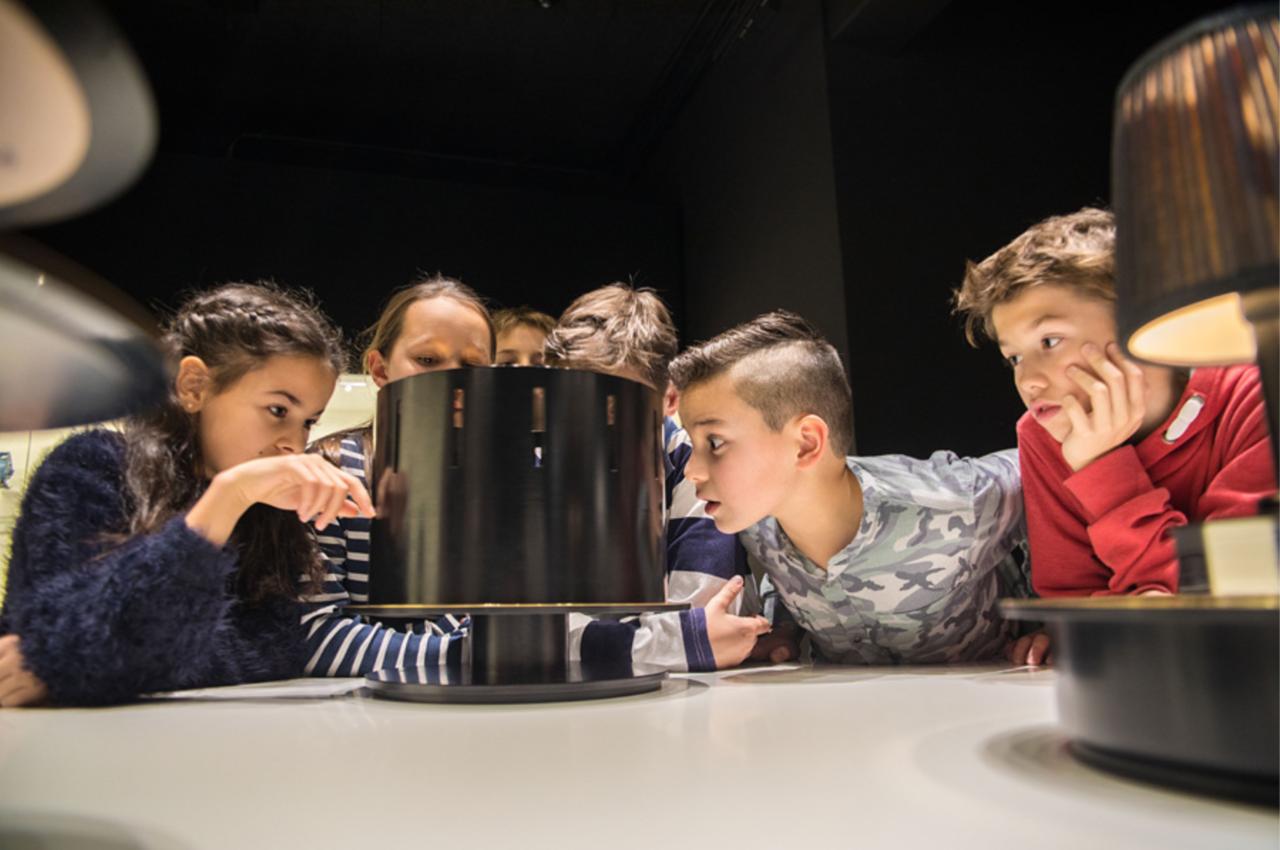 sechs Kinder sitzen an einem Tisch und schauen sich eine Lampe an