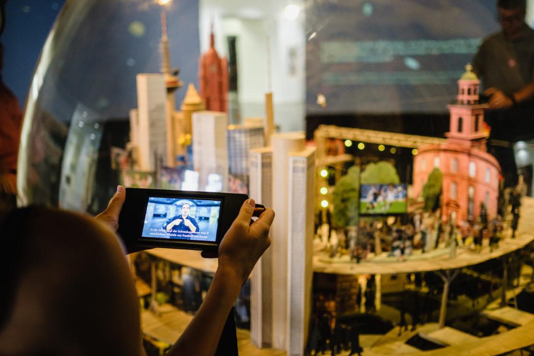 Auf einem digitalen Endgerät wird vor einem Ausstellungsexponat ein Film abgespielt.