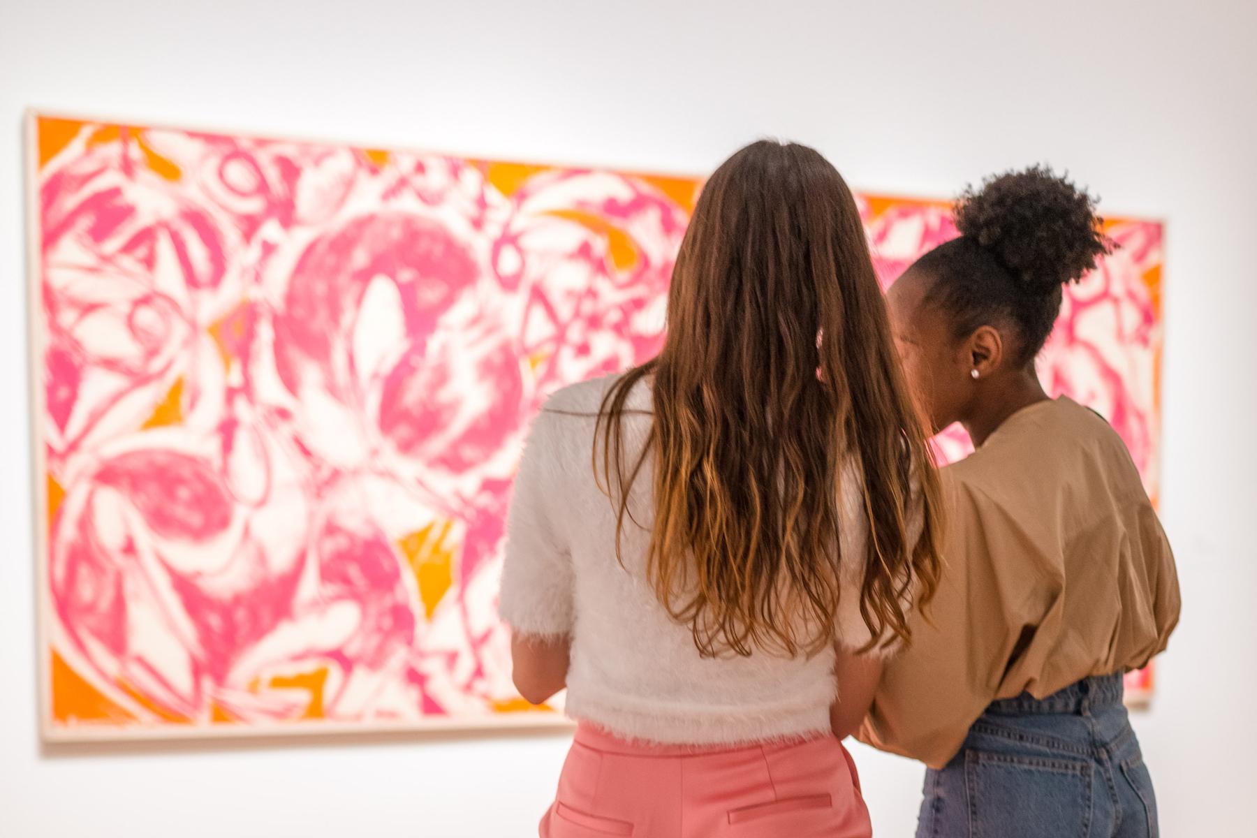 zwei Mädchen stehen vor einem Gemälde