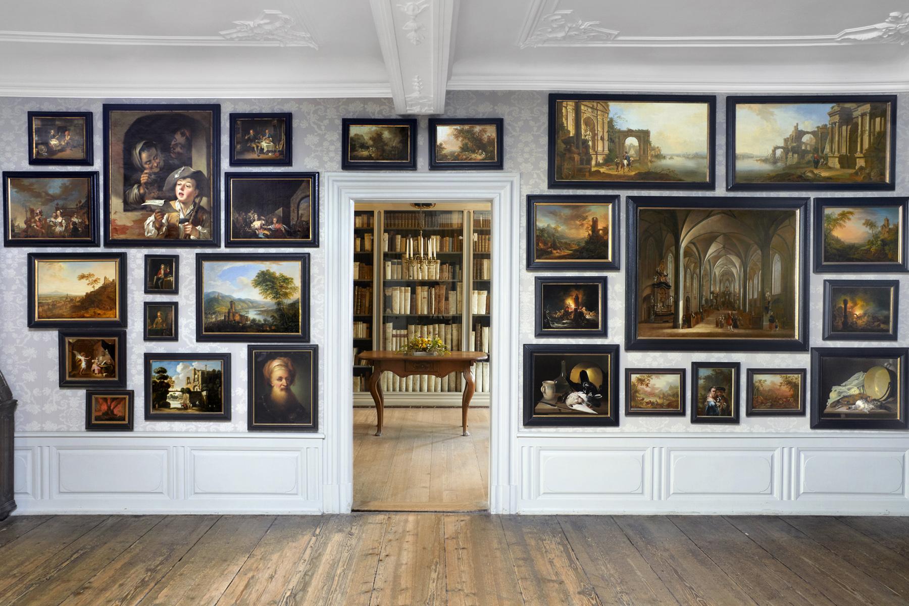 Frontaler Einblick in das Gemäldekabinett des Goethe Hauses. rechts und links hängen verschiedene Gemälde, gerade aus ist ein Zimmer mit verschiedenen Büchern zu sehen.