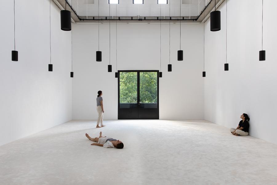 drei Junge Frauen liegen, sitzen und stehen in einem weißen, leeren Raum mit schwarzen Hängelampen.
