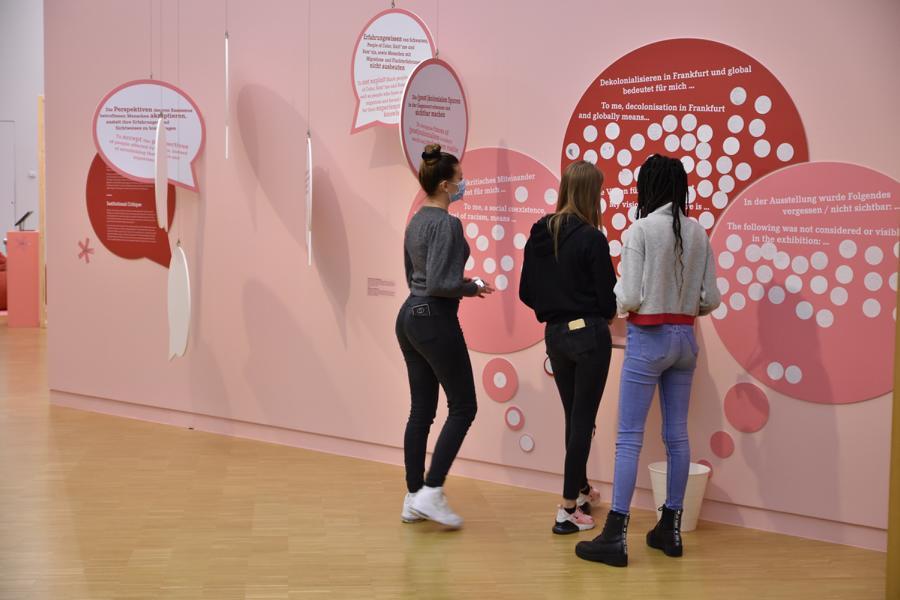 Drei junge Teenager stehen vor einer Ausstellungswand und lesen Texte.