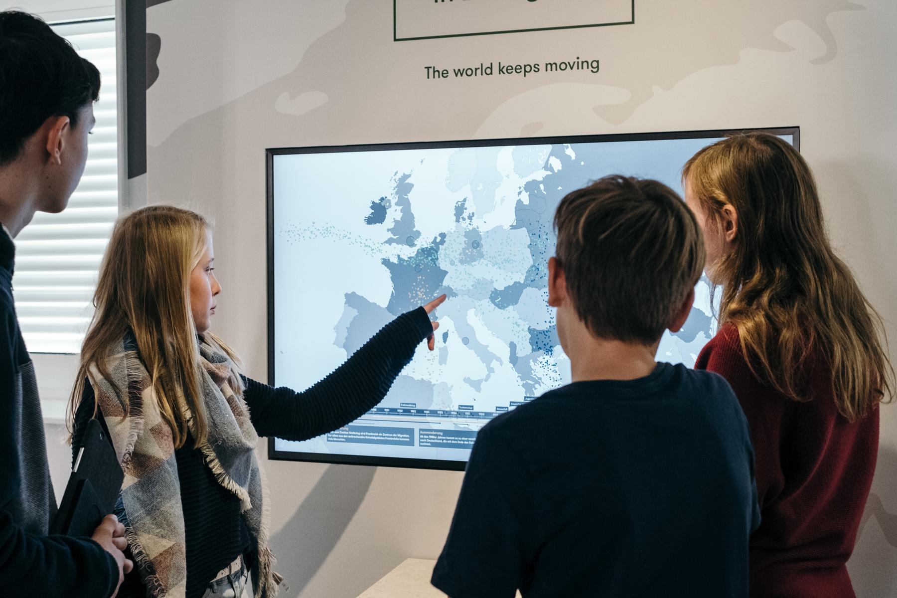 """4 Jugendliche Stehen vor einem Bildschirm mit einer Weltkarte, über dem Bildschirm stehen die Worte: """"The world keeps moving""""."""