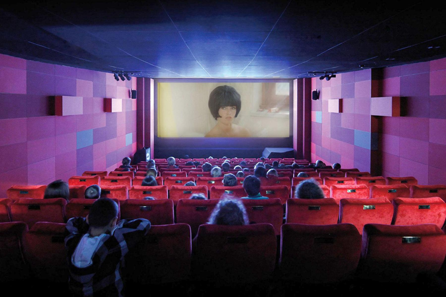 Kinder sitzen in einem Kinosaal mit roten Stühlen