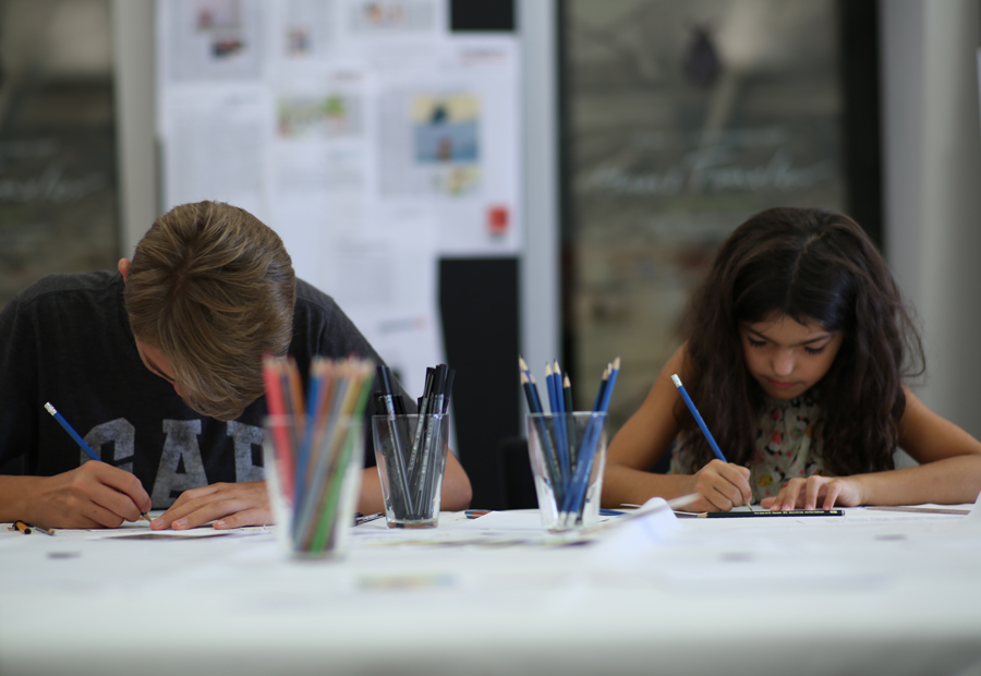 zwei Kinder, die an einem Tisch sitzen und zeichnen. In der Mitte des Tisches befinden sich drei Gläser mit Stiften.