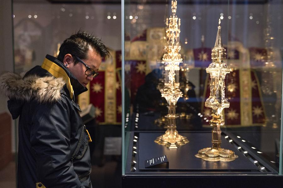 Ein junger Mann steht vor einer Vitrine und schaut sich die goldene Sammlung des Dommuseums an