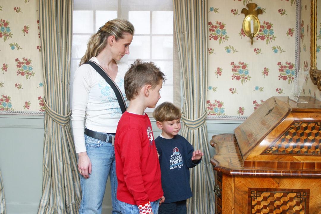 zwei Kinder und eine Frau vor einem Sekretär im Goethe Haus