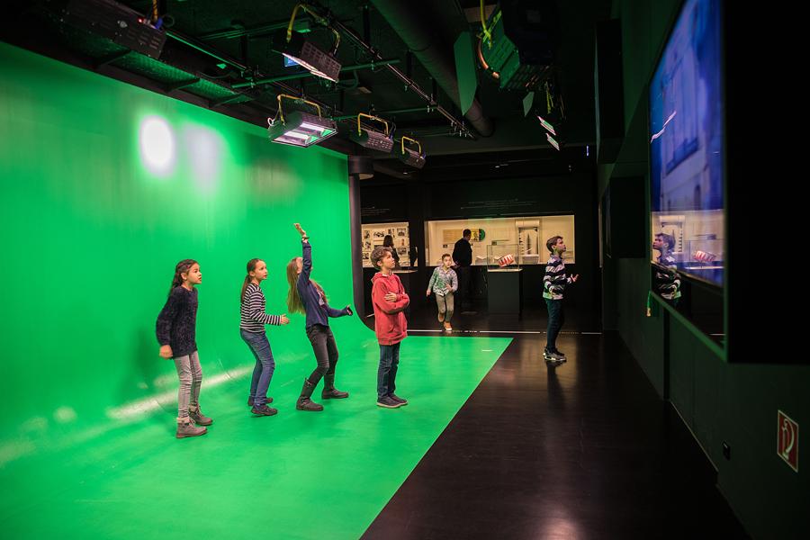 4 Kinder stehen in einem grünen Studio mit Scheinwerfer und Kamera