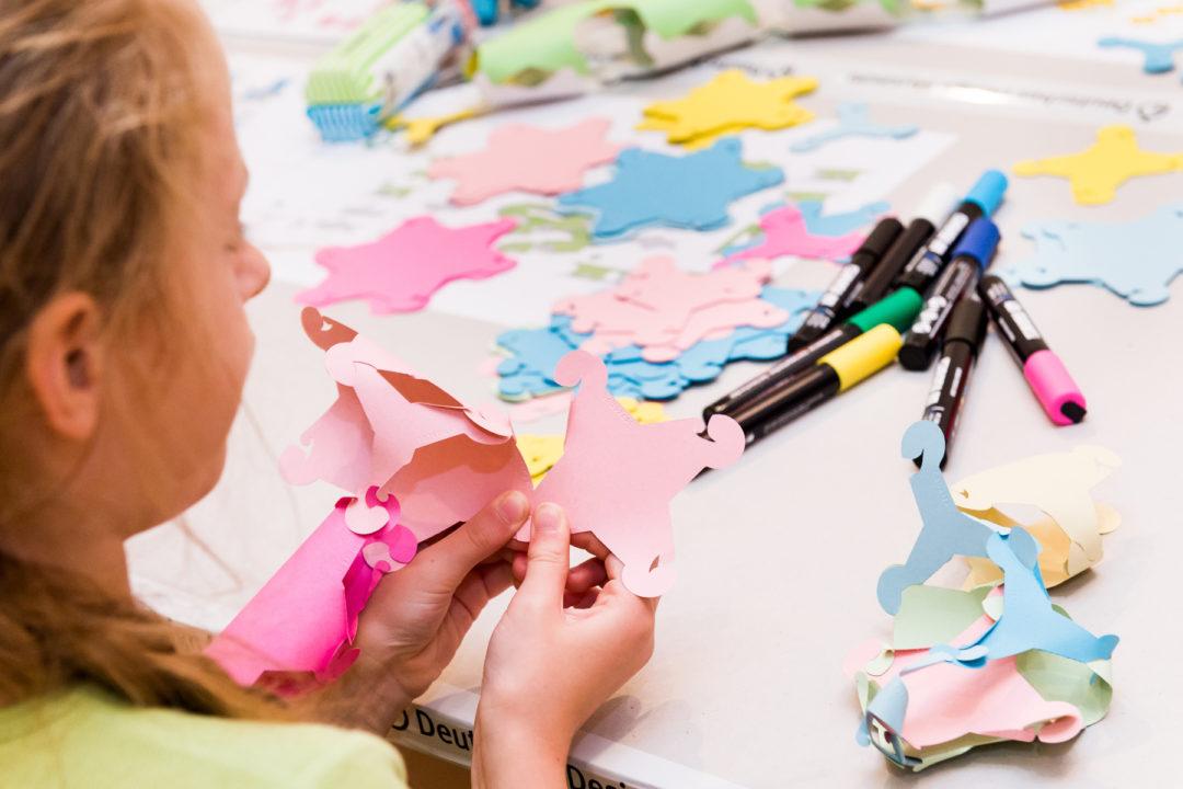 Ein Kind, welches bastelt. Vor ihr liegen Stifte und bunte Papiersschnipsel auf dem Tisch.