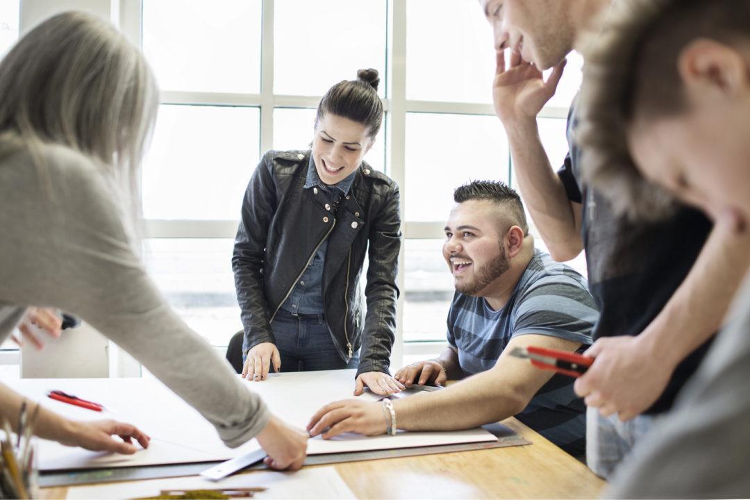 Jugendliche stehend und sitzend um einen Tisch herum, in der Mitte befindet sich ein großes weißes Blatt