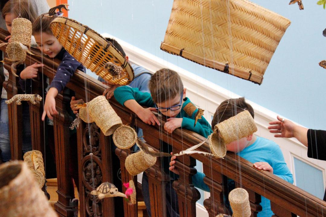 Mehrere Kinder auf einer Treppe, auf der Körbe und anderes Flechtwerk herunter hängen