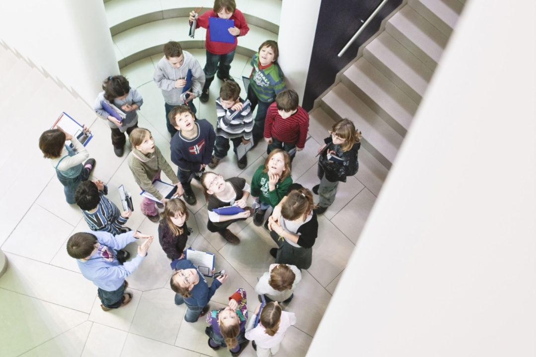 Mehrere Kinder mit Klemmbrettern in der Hand schauen nach oben in die Kamera
