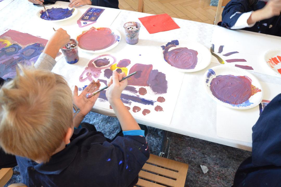 Kinder sitzen um einen weißen Tisch herum und malen mit Wasserfarben.
