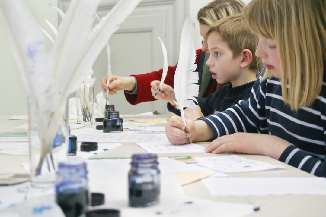 zwei Kinder und eine Frau, die an einem Tisch mit Federn und Tinte sitzen und schreiben bzw. zeichnen