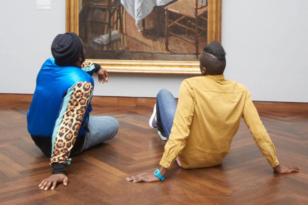 zwei Männer sitzen auf dem Boden vor einem Gemälde
