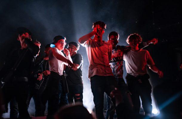 Ein Bild mit 8 Jungen Männern auf einer Konzertbühne